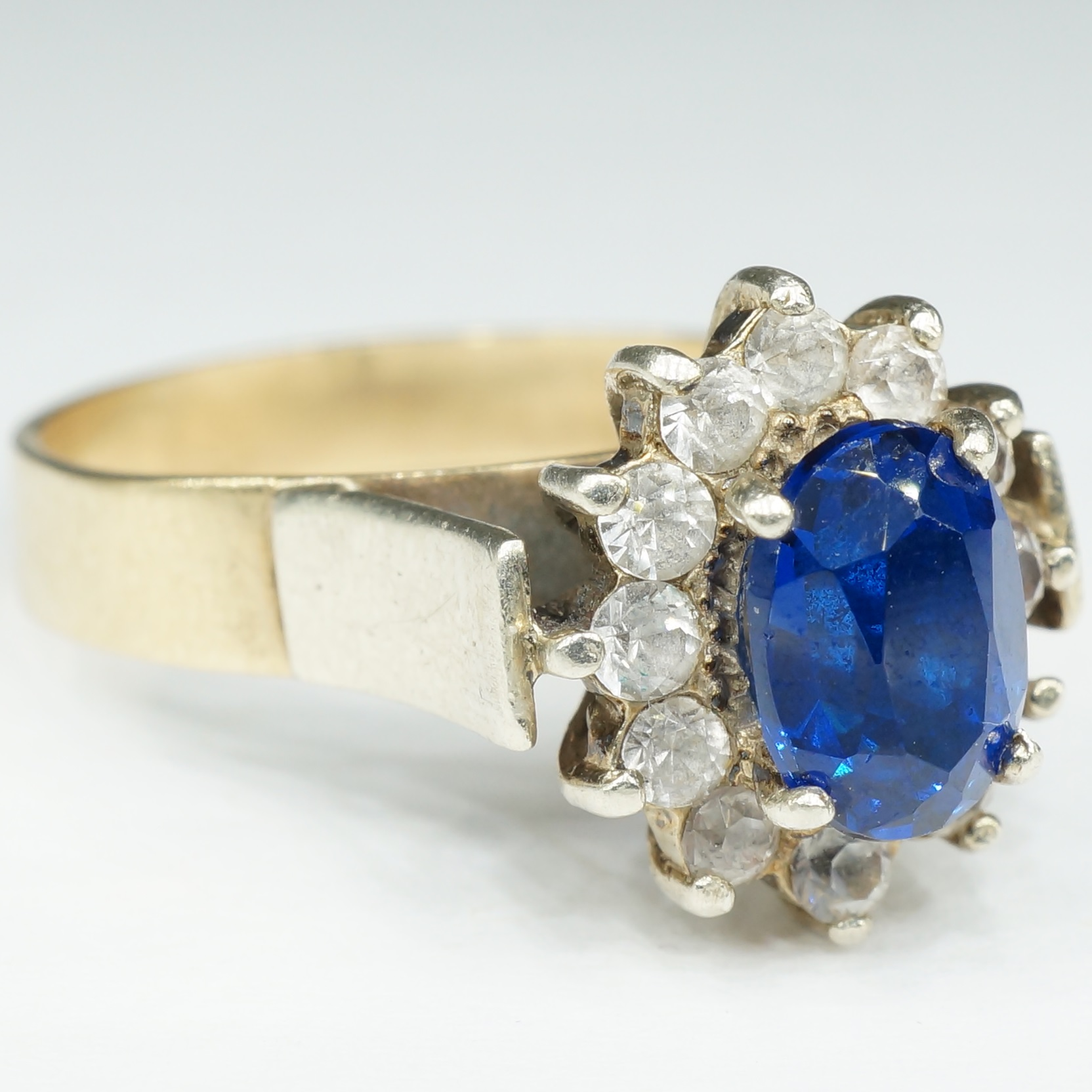'9ct Yellow Gold with White Gold Setting and Shoulders with Oval Facetted Blue Paste and White Imitations Stones Around'