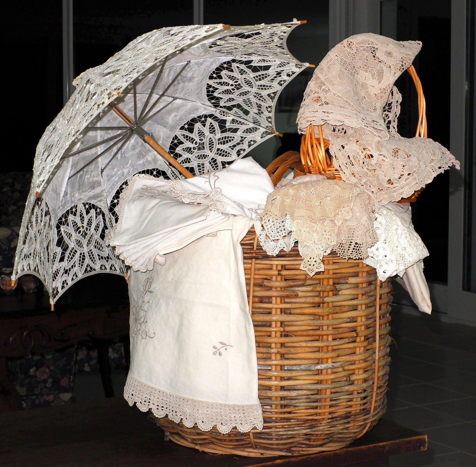 'Melange of Vintage and Antique Lace with Various Wicker Baskets and a Lace Parasol'