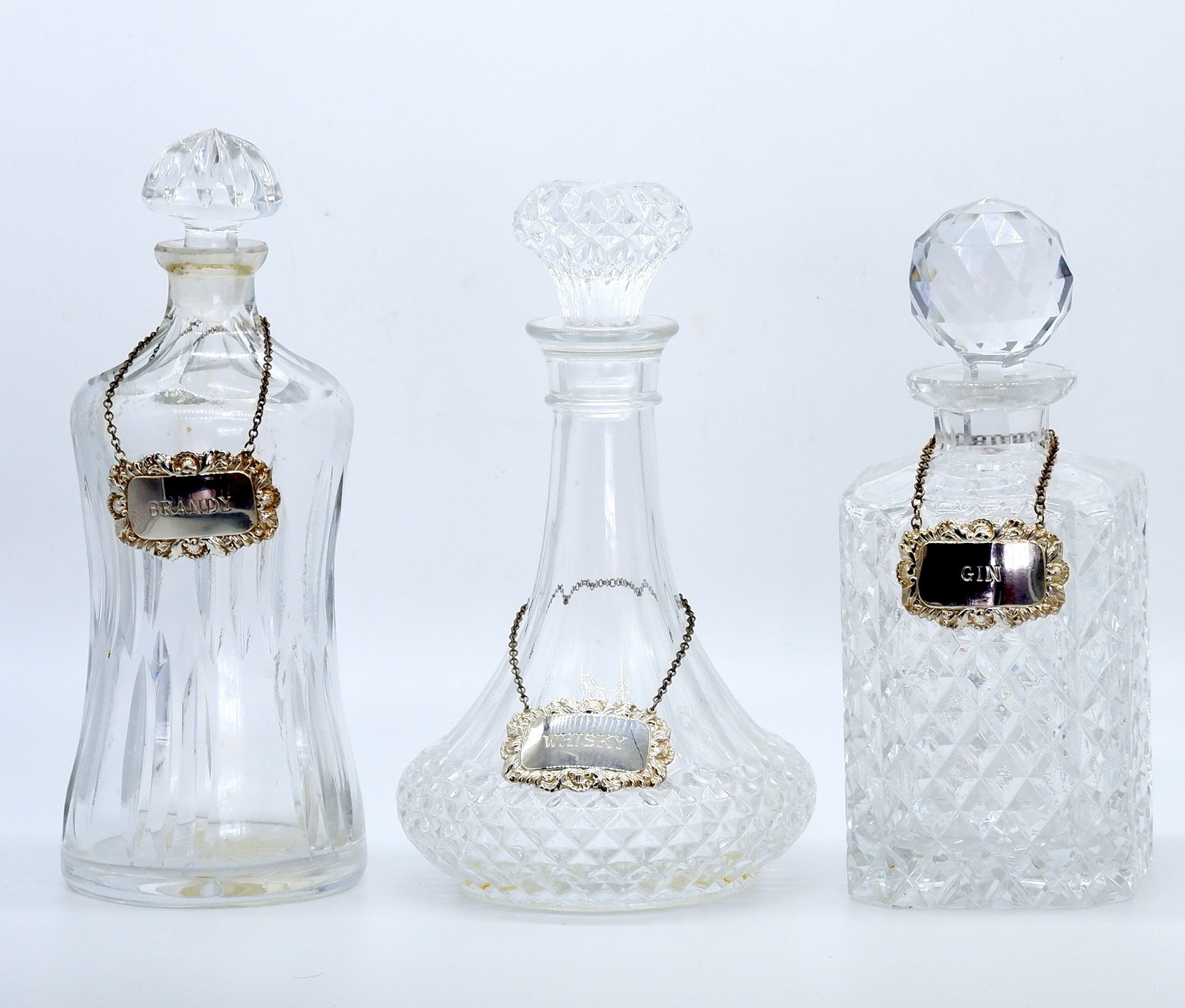 'Two Cut Crystal Decanters and One Moulded Glass Decanter'