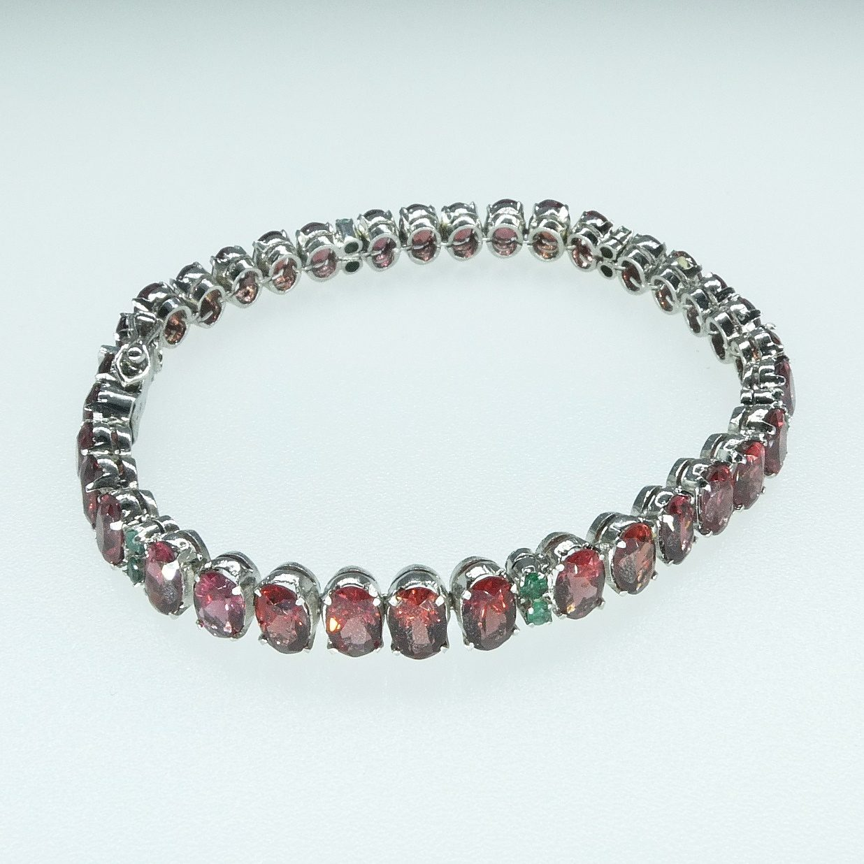 'Silver Tennis Bracelet with Oval Garnet and Small Round Emeralds'