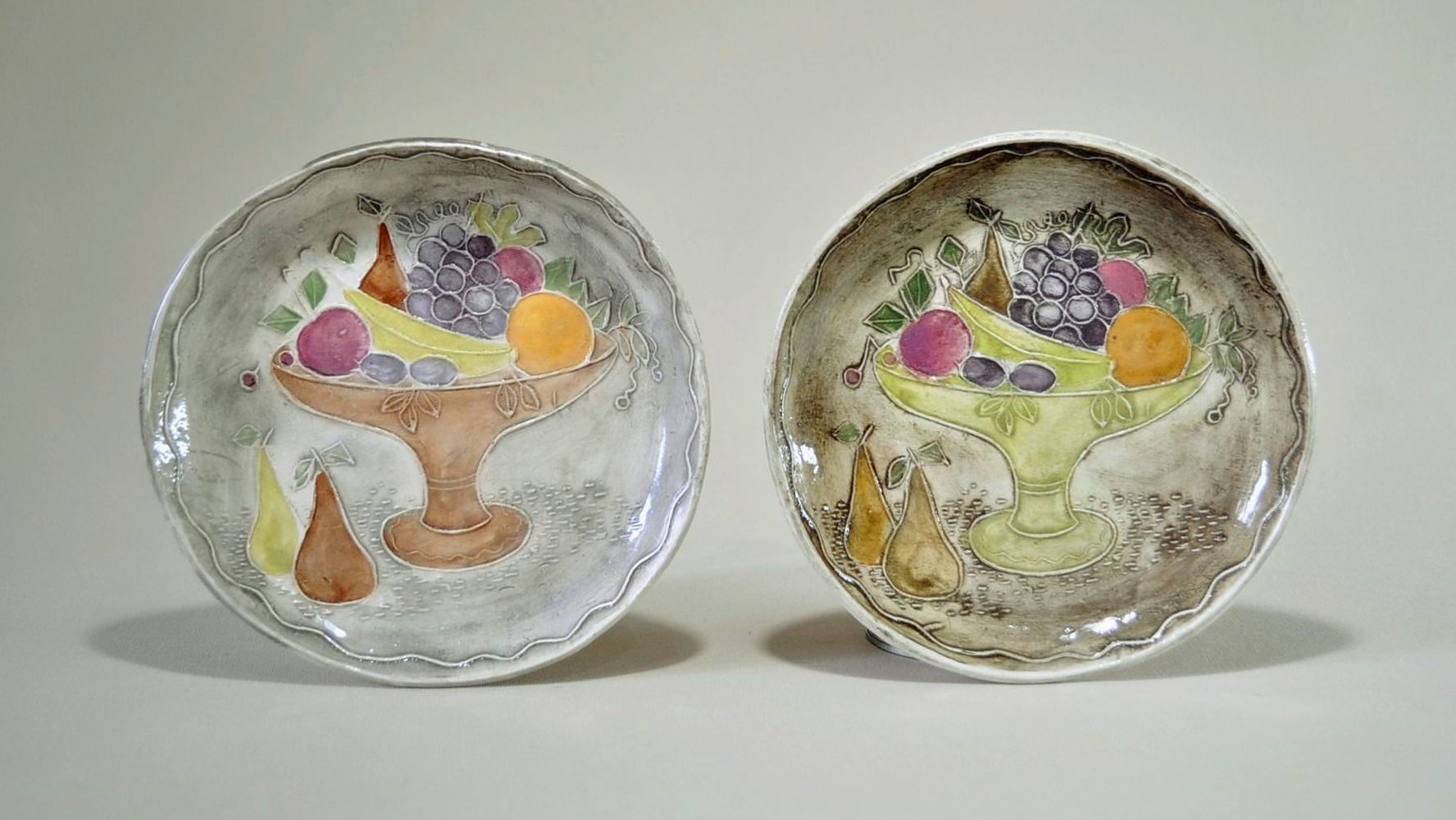 'JONES, Frances (1923-1999) (2) 2 Buff Earthenware Dishes. Press moulded with compote of fruit, multicoloured glaze decoration. Incised to base Frances Jones Studio Sydney '