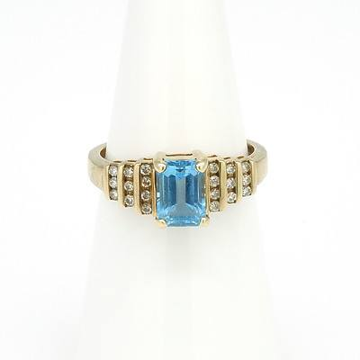 9ct Yellow Gold Ring with Emerald Cut Blue Topaz and Twenty Round Brilliant Cut Diamonds