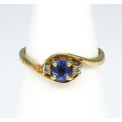 9ct Yellow Gold Ring with Oval Faceted Medium Blue Sapphire and Two Round Brilliant Cut Diamonds