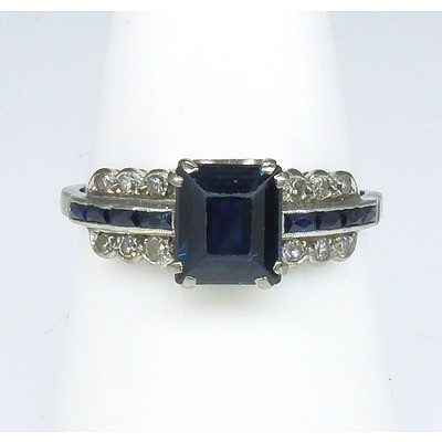 Antique 18ct Platinum White Gold Ring with One Carree Cut Deep Blue Sapphire. Each Shoulder with Four Step Cut Rectangular Sapphires Center and on each side Three Single Cut Diamonds in Bead Setting with Scalloped Edge