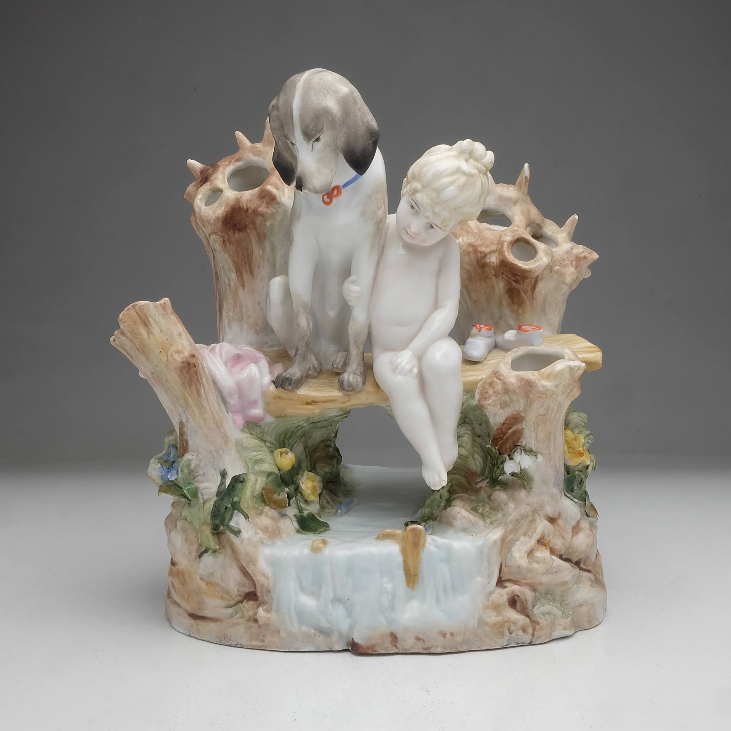 'German Königliche Porzellan-Manufaktur Porcelain Figure of Girl and Dog Sitting on a Bench over a Stream, 1123'