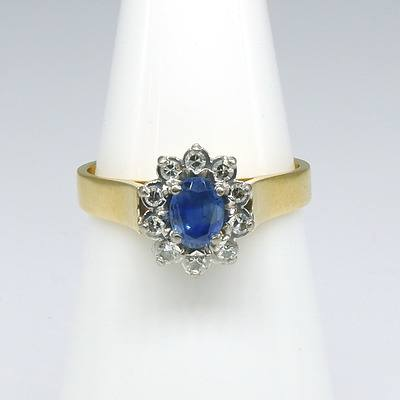 18ct Yellow and White Gold Ring, Oval Cluster with Centre Medium Blue Ceylonese Type Sapphire and Ten Single Cut Diamonds in Claw Setting