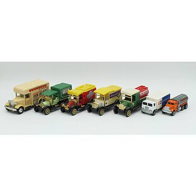 Seven Medium and Small Sized Toy Trucks Including; Gasoline, North American Van Lines, Australia Farm Products, Shop At Home Lighton Market and More
