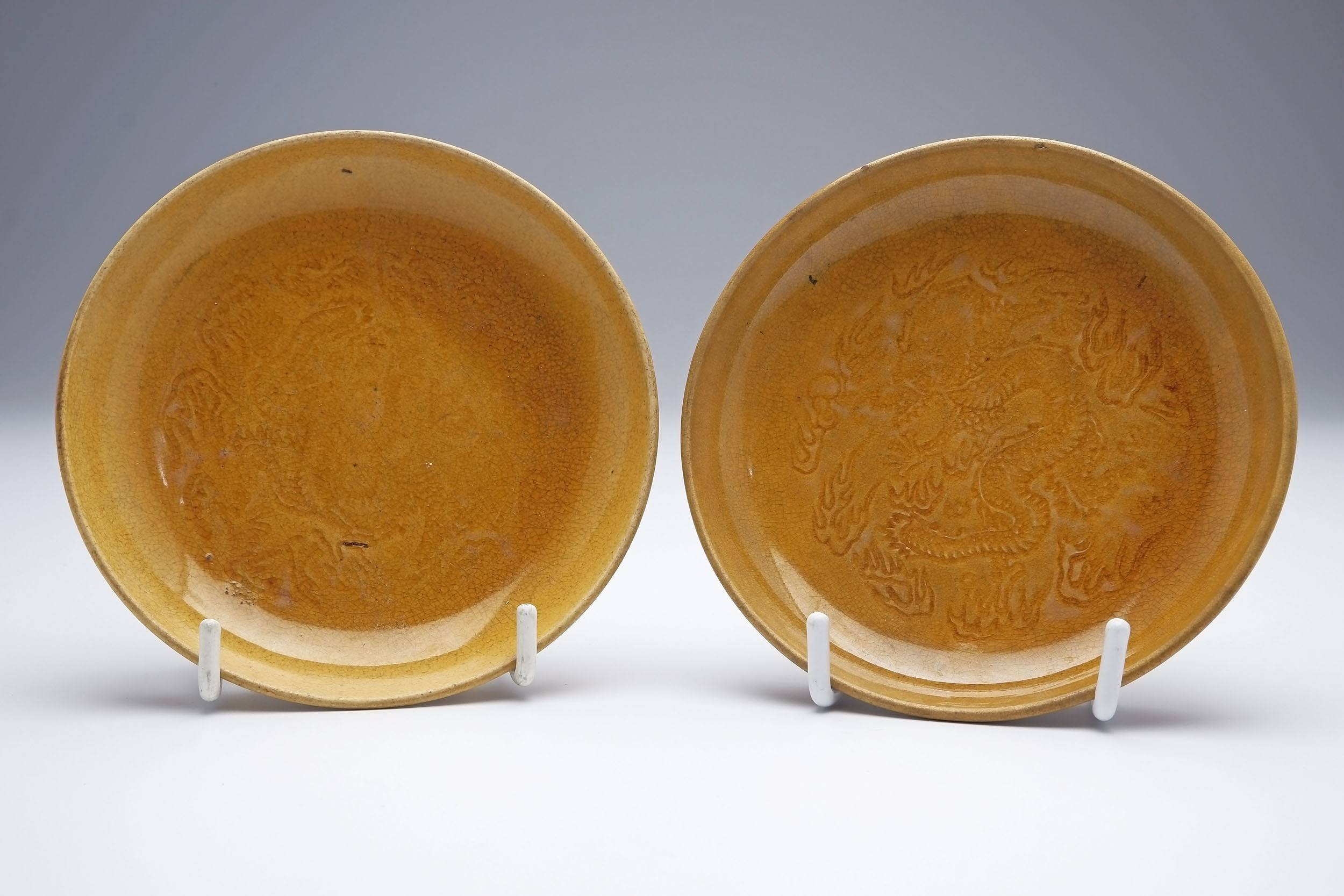 'Pair of Chinese Soft Paste Yellow Glaze Saucer Dishes with Stamped Dragon Decoration, Late Qing'
