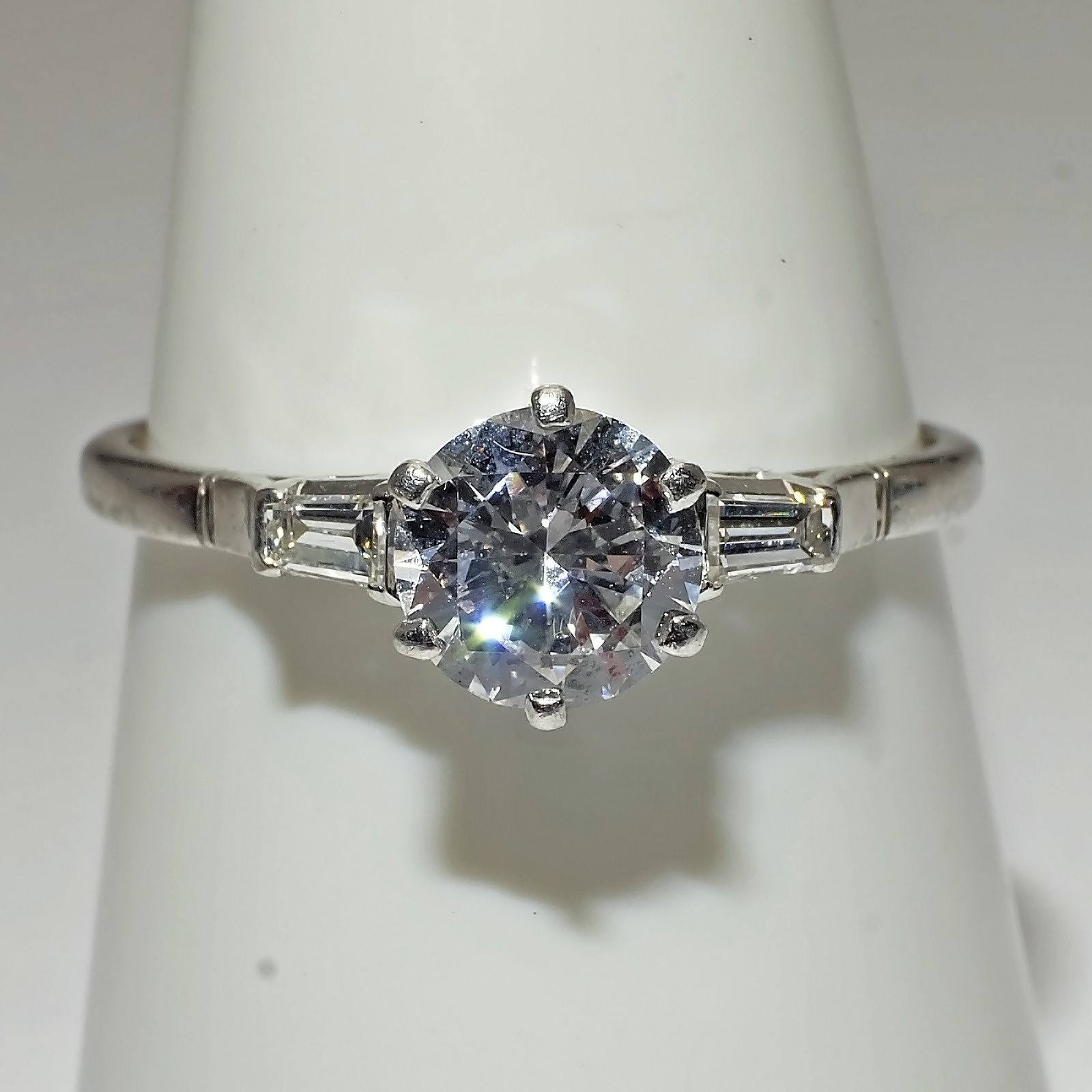 'Platinum Ring with at Centre a Round Brilliant Cut Diamond 0.90ct (F/G VS2) in a Six Claw Pierced Setting, On either Side a Tapered Baguette Diamond'