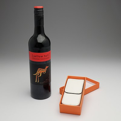 White leather pen case and bottle of wine
