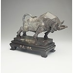 A Chinese Cast Resin Statue of a Charging Buffalo on a Wooden Stand